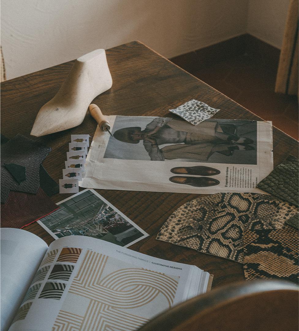 Mesa de trabajo con recortes materiales y revistas de diseño de calzado